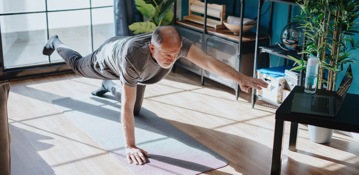 Older man doing yoga at home