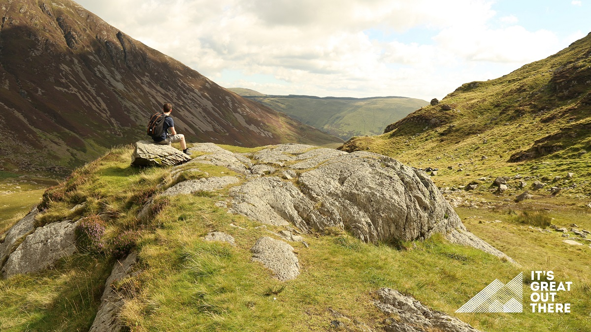 A young man wearing a rucksack and sitting on rock looking over valley