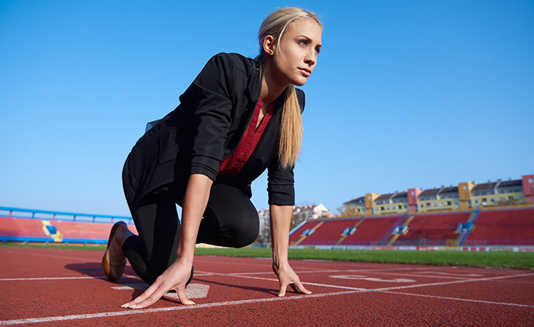 Woman on a running track preparing for a sprint (Shutterstock)