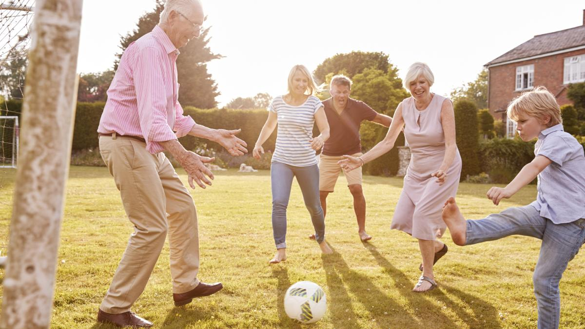Intergenerational family plays soccer on the lawn