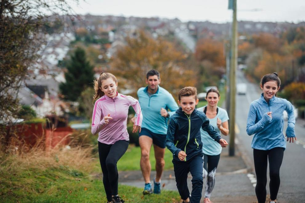 A family of four running together outside