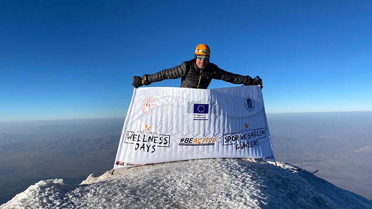 Man holding Turkey EWOS 2020 flag